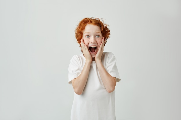 Opgewonden roodharige jongen met sproeten die gezicht met handen vasthoudt, met een gelukkige uitdrukking en opende mond nadat ouders hem snoep hadden gegeven.