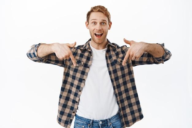 Opgewonden roodharige man die met zijn vingers naar beneden wijst, geweldige nieuwe promo-aanbieding laat zien, advertentie balg, website of winkel aanbeveelt, staande over witte muur