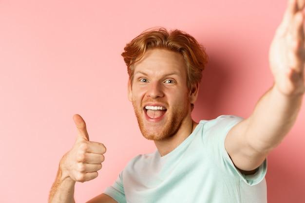 Opgewonden roodharige man toerist die selfie neemt en duim omhoog laat zien, camera vasthoudt met uitgestrekte hand, staande over roze achtergrond