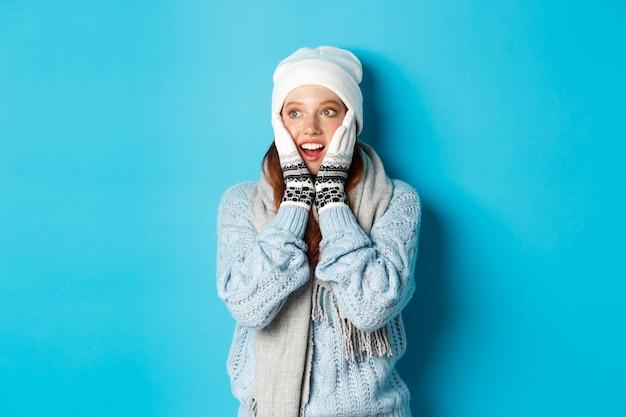 Opgewonden roodharige meisje staren naar het logo, gekleed in winterkleren, muts, handschoenen en trui, staande over blauwe achtergrond