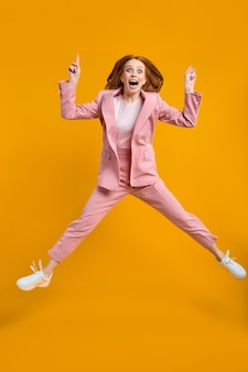 Opgewonden roodharige succesvolle zakenvrouw springen met opgeheven vingers opdagen geïsoleerd op gele ...