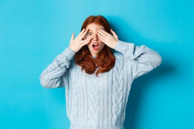 Opgewonden roodharige tienermeisje opent ogen om vakantieverrassing te zien, cadeautjes te ontvangen, verbaasd naar de camera te kijken, staande over blauwe achtergrond.