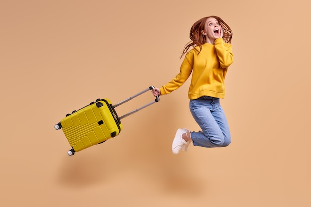 Opgewonden roodharige vrouw gaat op vakantie springen met een glimlach op het gezicht met gele handbagage ...