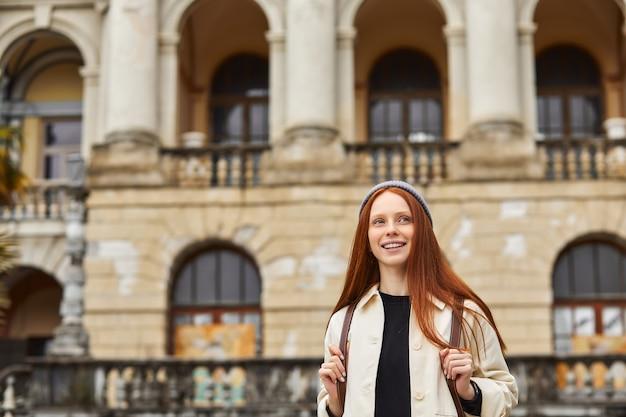 Opgewonden roodharige vrouw toerist loopt op oude sites excursies naar oude steden vrouwelijke toerist kijkt naar attractie vrouw op de achtergrond van een prachtig gebouw historische plaats