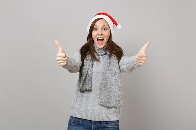 Opgewonden santa meisje in grijze trui sjaal kerstmuts houden mond wijd open met duimen omhoog geïsoleerd op een grijze achtergrond. gelukkig nieuwjaar 2019 viering vakantie partij concept. bespotten kopie ruimte.