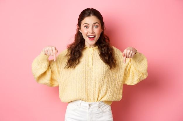 Opgewonden schattig meisje met advertentie wijzende vingers naar beneden en lachend naar de camera die logo demonstreert tegen de roze muur