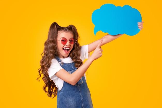 Opgewonden schattig tienermeisje in trendy outfit wijzend op blauwe tekstballon