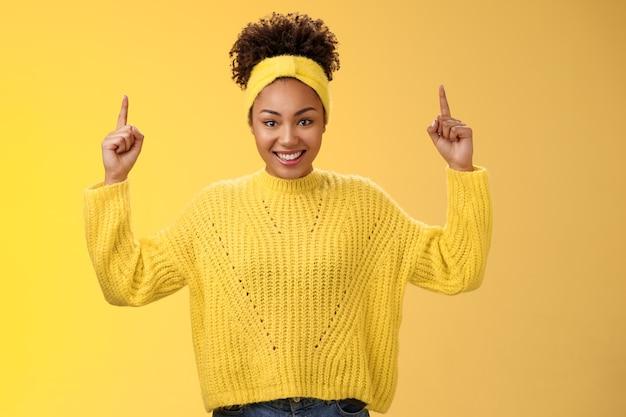 Opgewonden schattig vrouwelijk afro-amerikaans jong meisje afro kapsel in hoofdband trui wijzende vinger...