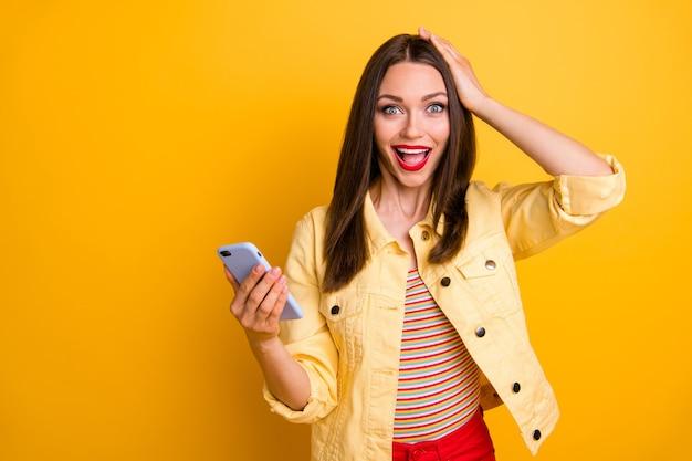 Opgewonden schattige vrolijke vriendin die haar hoofd vasthoudt bij het typen van berichten aan vrienden met een gadget die emotioneel geïsoleerde levendige kleurenmuur schreeuwt