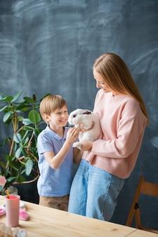 Opgewonden schattige zoon aaien konijn gehouden door moeder tegen schoolbord, pasen viering concept