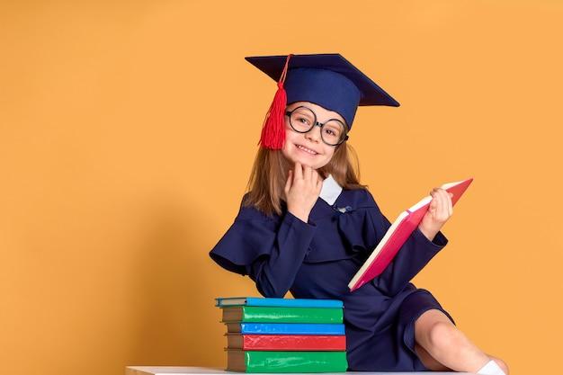 Opgewonden schoolmeisje in afstuderen outfit studeren met schoolboeken