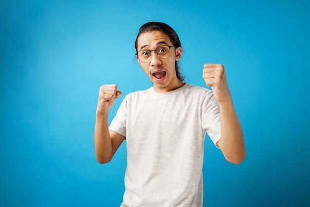 Opgewonden schreeuwende wow jonge man in wit t-shirt