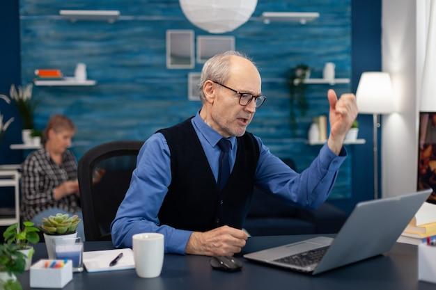Opgewonden senior man die goed nieuws viert terwijl hij vanuit thuiskantoor op een laptop werkt