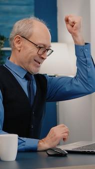 Opgewonden senior man voelt zich extatisch bij het lezen van geweldig online nieuws op een laptop die vanuit huis werkt