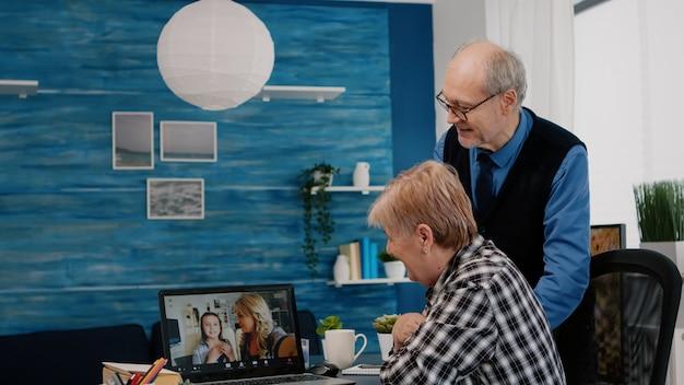 Opgewonden senior vrouw en haar man hebben videoconferentie op laptop, praten met verre neven zitten in de woonkamer. online bellen met dochter en nichtje via moderne online communicatie