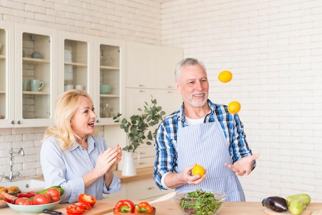 Opgewonden senior vrouw klappen terwijl haar man met citroenen in de keuken jongleren