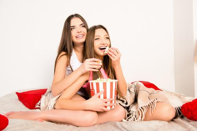 Opgewonden sexy meisjes die film kijken en popcorn eten