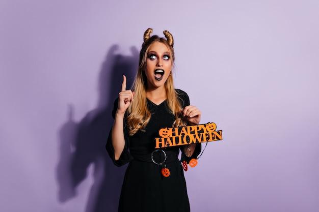 Opgewonden slank meisje dat op halloween wacht. enthousiaste blonde vrouw feest voorbereiden.