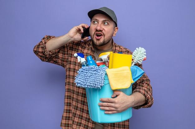 Opgewonden slavische schonere man die schoonmaakapparatuur vasthoudt en aan de telefoon praat