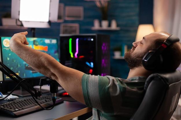 Opgewonden speler die belangrijke online esport-competitie wint van space shooter die op een krachtige computer speelt. professionele professionele gamer die videogames streamt met professionele microfoon en headset