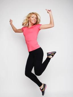 Opgewonden sportieve vrouw springen.