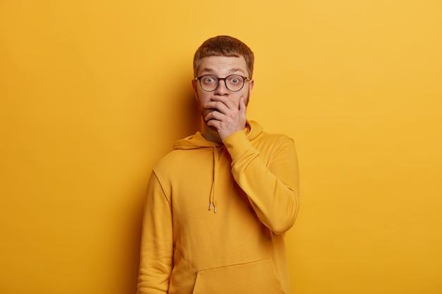 Opgewonden sprakeloze jongeman bedekt mond en hapt van grote verwondering, hoort verbluffend nieuws, draagt een transparante bril en hoodie, kijkt angstig en paniekerig, poseert binnen over gele muur