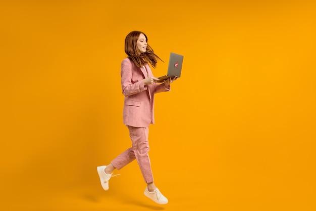 Opgewonden springende vrouw met laptop geïsoleerd op gele studio achtergrond moderne technologieën vrijheid van keuzes concept emoties concept met behulp van laptop voor werk en plezier tijdens de vlucht