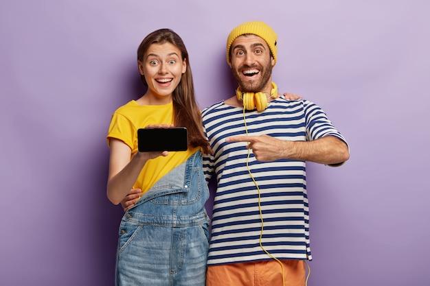 Opgewonden stijlvolle paar poseren met smartphone