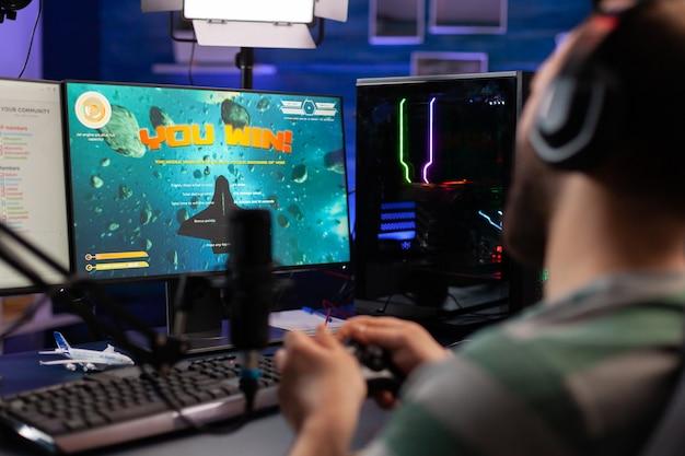 Opgewonden streamer die online virtuele gamecompetitie wint van space shooter die op een krachtige computer speelt. professionele gamer met joystick voor space shooter-kampioenschap zittend op gaming-bureau