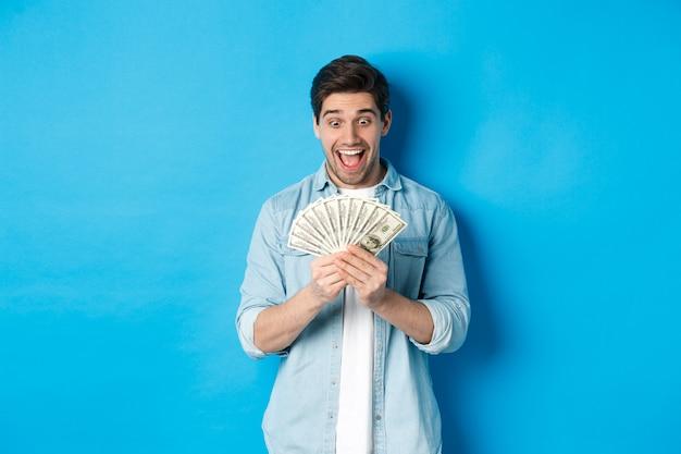 Opgewonden succesvolle man die geld telt, tevreden naar contant geld kijkt en glimlacht, staande over blauwe achtergrond