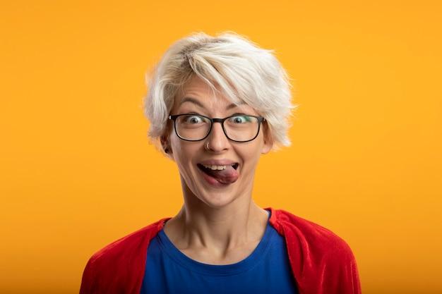 Opgewonden supervrouw met rode cape in optische glazen steekt tong uit die op oranje muur wordt geïsoleerd
