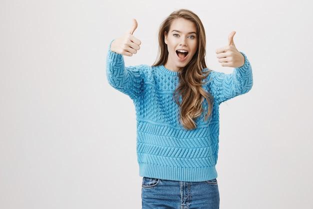 Opgewonden tevreden vrouw thumb-up in goedkeuring