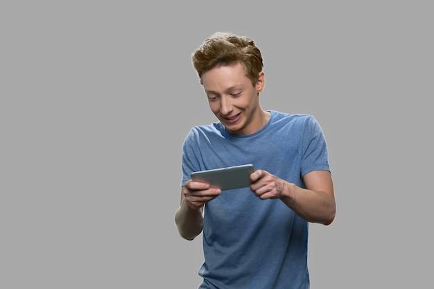 Opgewonden tiener mobiele spel spelen. expressieve tiener man met behulp van smartphone tegen een grijze achtergrond.