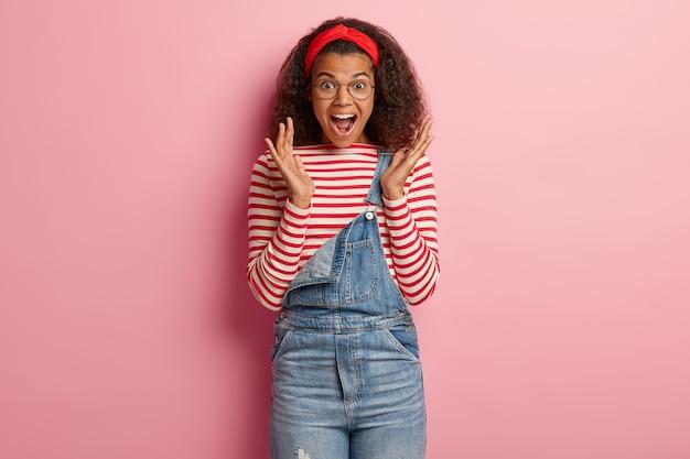 Opgewonden tienermeisje poseren in overall met krullend haar