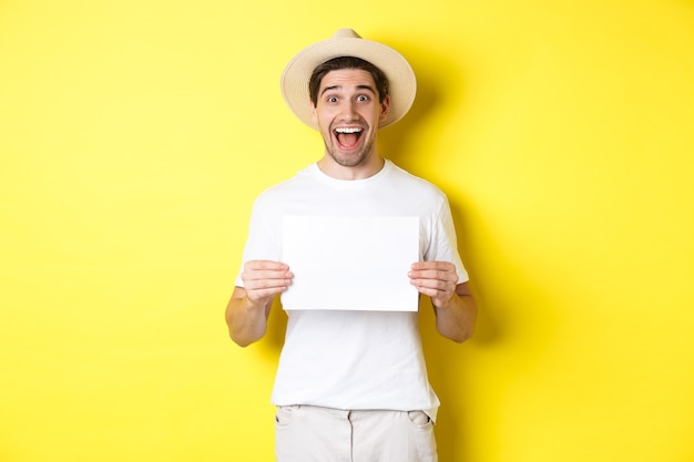 Opgewonden toerist die uw logo of teken op een blanco vel papier laat zien, glimlachend verbaasd, staande tegen een gele achtergrond.