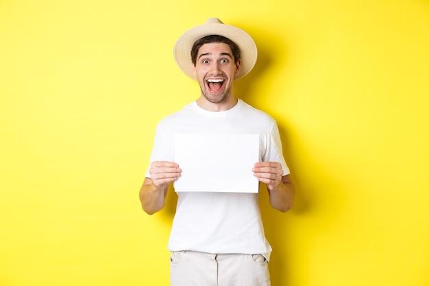 Opgewonden toerist die uw logo of teken op een blanco vel papier laat zien, verbaasd glimlacht, staande tegen een gele achtergrond.