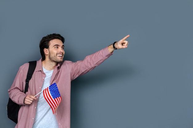 Opgewonden toerist. opgetogen gelukkig aardige man die een amerikaanse vlag vasthoudt en met zijn hand wijst terwijl hij naar een historisch monument kijkt