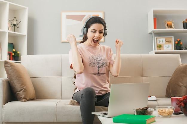 Opgewonden tonen ja gebaar jong meisje met koptelefoon gebruikte laptop zittend op de bank achter de salontafel in de woonkamer