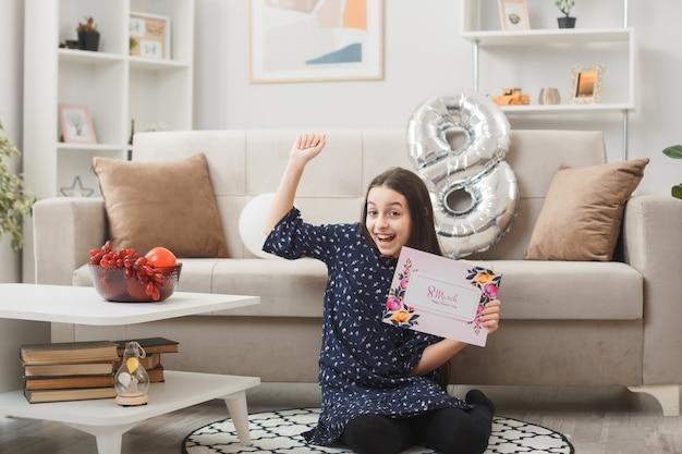 Opgewonden toont ja gebaar meisje op gelukkige vrouwendag zittend op de vloer met ansichtkaart in de woonkamer