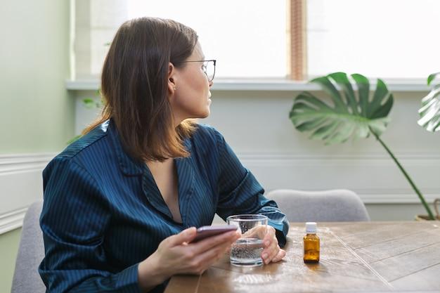 Opgewonden trieste volwassen vrouw die smartphone leest. vrouw in pyjama om thuis te zitten, drinkwater met kalmerende druppels. fysieke en psychologische geestelijke gezondheid van mensen van middelbare leeftijd, kopieer ruimte