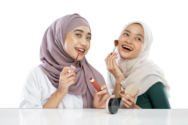 Opgewonden twee gesluierde meisjesvloggers die een penseel vasthouden en lippenstift aanbrengen bij het maken van videovlog