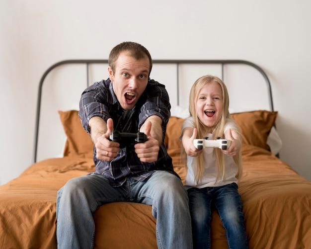 Opgewonden vader en kind spelen met joystick