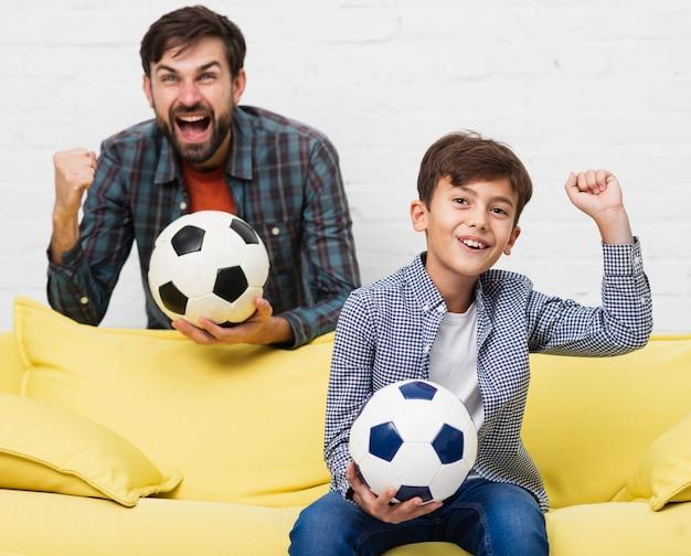Opgewonden vader en zoon kijken naar een voetbalwedstrijd