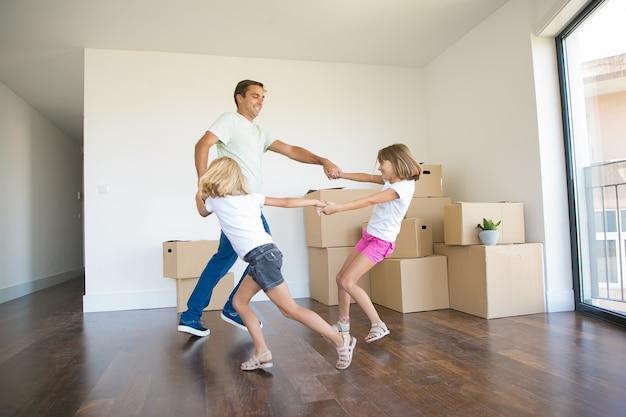 Opgewonden vader ronddansen met twee meisjes tussen uitgepakte dozen