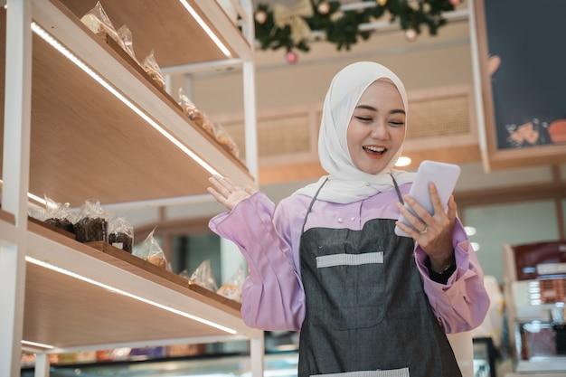 Opgewonden van aziatische hijab-vrouw heft haar arm op terwijl ze naar haar telefoon kijkt. zakelijke ondernemer in haar kleine winkel