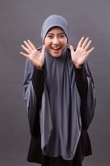 Opgewonden, verbaasde, blije, lachende moslimvrouw met hijab of hoofddoek