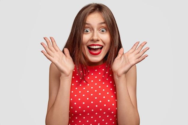 Opgewonden verbaasde jonge schattige europese vrouw grijpt handen in de buurt van gezicht, laat kaak vallen van opwinding, kan niet geloven dat ze beroemdheid ziet