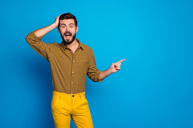Opgewonden, verbaasde man duiden op ongelooflijke advertenties promotie onder de indruk schreeuw wow omg wijs wijsvinger copyspace stel voor kies dragen broek geruit glans geïsoleerde blauwe kleur