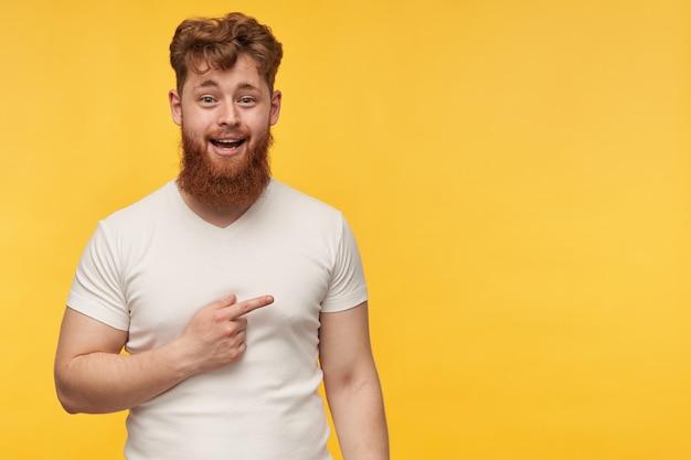 Opgewonden verbaasde man met rood haar en baard draagt een blanco t-shirt wijst naar rechts op kopie ruimte