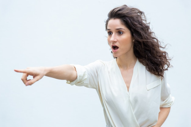 Opgewonden verbaasde vrouw met open mond wijzende vinger weg